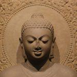 gray concrete buddha statue in white floral textile